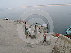 Father and children untangle fishing net near Assi Ghat Varanasi India