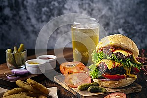 Fresh and juicy hamburger. Cheese burger with beef or bacon, patty tomato, onion ring and sparkling water or beer