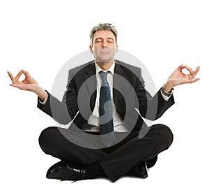 Geschäftsmann, der in Yogastellung sitzt