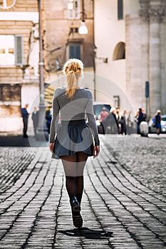 Girl walking on the street in the city wearing a skirt. Back.