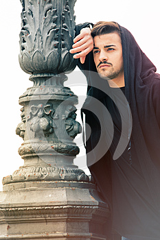Gorgeous young man leaning against a old lamppost