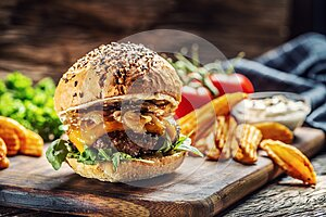 Hamburger with caramelized onion, arugula and melted cheese