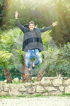 Happiness success of a young man outdoors. Jumping for joy