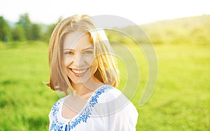 Happy beautiful young woman laughing and smiling on nature