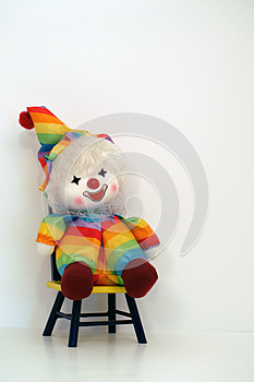 Happy faced clown doll sitting on a time out chair