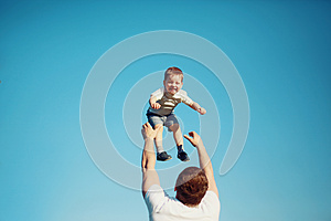 "Happy joyful child, father fun throws up son in the air, summer"" border=""0"