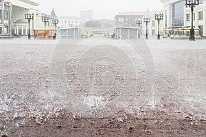 Heavy rain in the city. Town square. Close up sidewalk with rectangle tiles under water