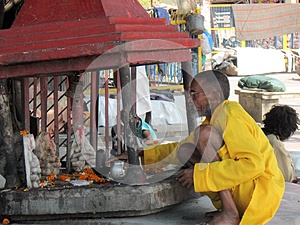 Indian Sadhu (holy man) tending a street shrine