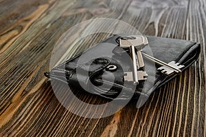Keys and purse, black, on the wooden surface of the table