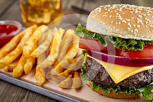Hamburger on sesame seed bun with fries