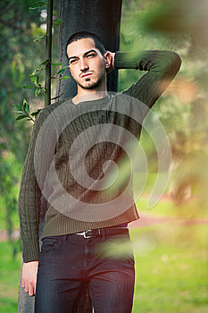 Model man short hair leaning against a tree in a nature scene