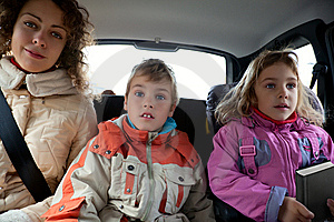 Mother with children sit on back seat of car