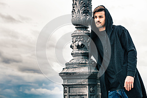 Mysterious and handsome young man model with hoody. Cloudy sky