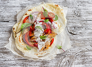Naan bread and chicken vegetables stir fry in light wood rustic background.