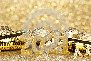 New Years 2021 gold numbers and decor with twinkling light background
