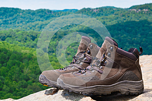 Pair of hiking boots in front of mountain forest