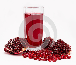 Pomegranate juice in glass and pomegranates  on white
