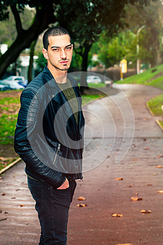 Portrait of young beautiful man outdoors, path in the park