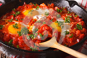 shakshuka fried eggs with sauce close up in a frying pan. horizontal