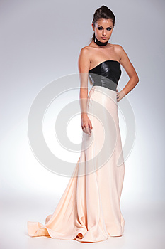 Side view of a young sexy woman in a long evening dress