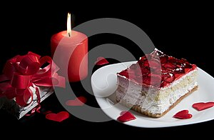 Strawberry cake with red berries on white plate, hearts and candle burning isolated on black background. Holiday food