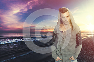 Stylish man with hooded sweatshirt the sea. Colorful sunset