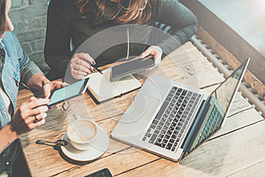 Teamwork. Two young businesswomen sitting at table in coffee shop, look at your smartphone screen and discuss business strategy.