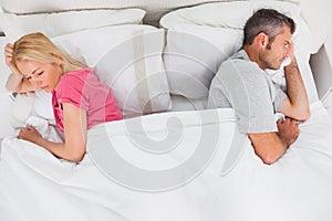Upset couple lying back to back