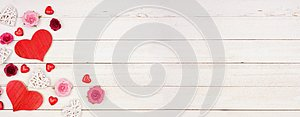 Valentines Day banner with corner border of hearts, flowers and decor against a white wood background with copy space