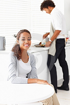 Woman sitting at a table  husband preparing food f