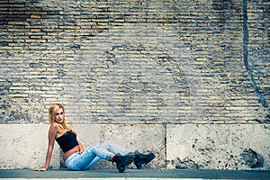 Young beautiful blonde girl sitting, old brick wall. Youth fashion.