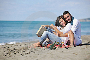 Young couple enjoying picnic on the beach
