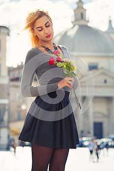 Young girl in love. Blonde teenager with roses in hand.