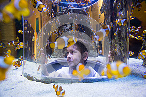 Young man looking at fish into a circular tank
