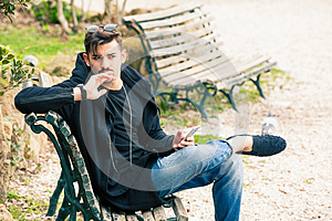 Young man sitting on the bench thinking waiting with phone in hand