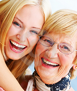 A young woman hugs an older happy elderly woman