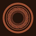 Traditional simple meander. Terrakota circle frame on the brown background. Ancient Greek ornament.