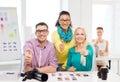 équipe de sourire avec les photos imprimées fonctionnant dans le bureau Photographie stock