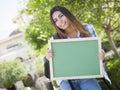 étudiante de sourire holding blank chalkboard de métis Image stock