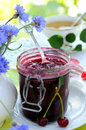 вerry jam jar of cherry and a bouquet of cornflowers on a table Stock Image