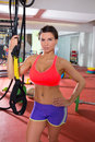 image photo : Crossfit fitness woman standing at gym holding trx
