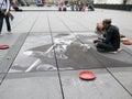 пасте ьный ху ожник рисует чар и чап ина на тротуаре пере фонтаном Стоковые Фотографии RF