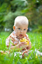 сhild with pear on a grass boy Royalty Free Stock Image