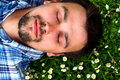 уoung man lying in grass with flowers young bearded brunet blue shirt is closing his eyes and many little white close up Stock Photo