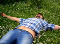 уoung man lying in grass with flowers young bearded brunet blue shirt is many little white relax and freedom feelings Stock Photos