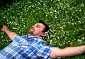 уoung man lying in grass with flowers young bearded brunet blue shirt is smiling and many little white diagonal composition relax Royalty Free Stock Images