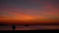 与使用在岸的两个儿童的剪影的日落 免版税库存照片