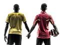 两个人站立的足球运动员拿着手剪影 库存照片