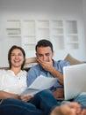 在家研究便携式计算机的 松的  夫妇 免版税库存照片