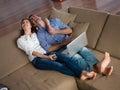 在家研究便携式计算机的 松的  夫妇 库存照片